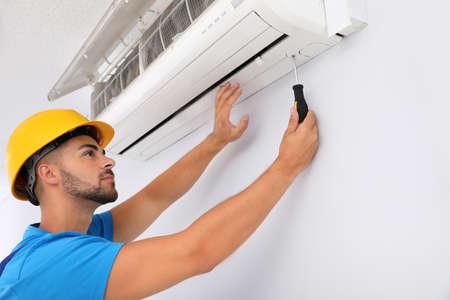 Professionele technicus die moderne airconditioner binnenshuis onderhoudt