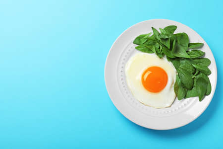 Plate of fried egg and spinach on light blue background, top view with space for text. Healthy breakfast