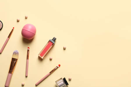 Flat lay composition with makeup brushes on beige background. Space for text