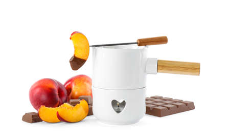 Fondue pot with chocolate and fresh peaches on white background