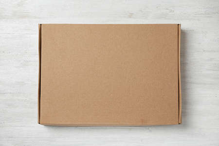 Cardboard box on white wooden background, top view
