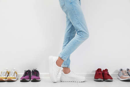 Woman trying on different shoes near white wall, closeup