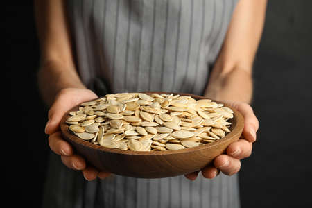 Young woman with bowl of raw pumpkin seeds on black background, closeup
