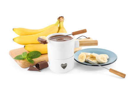Fondue pot with chocolate and banana on white background Imagens