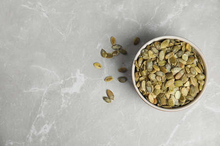 Bowl of raw pumpkin seeds on light grey marble table, top view. Space for text Фото со стока - 130074660