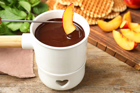 Dipping slice of peach into fondue pot with chocolate on wooden table, closeup
