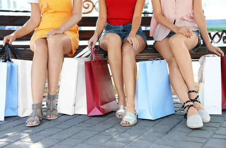 Young women with shopping bags sitting on bench in park