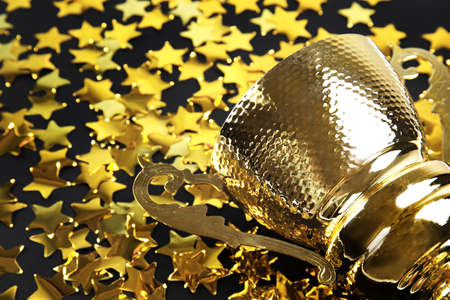 Gold trophy cup and confetti on black background, closeup. Space for text
