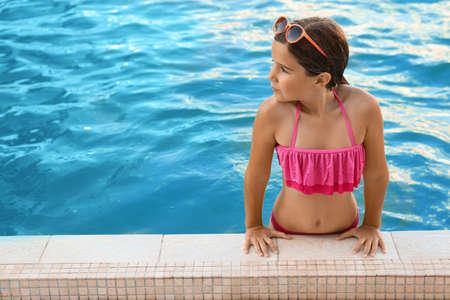 Feliz linda chica con gafas de sol en la piscina
