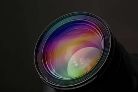 Lens of professional camera on black background, closeup