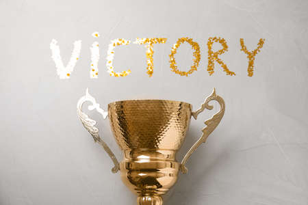 Gold trophy cup and word VICTORY made with confetti on light grey stone background, flat lay