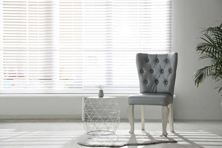 Stylish silver chairs and table near window in room Stok Fotoğraf