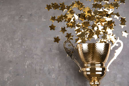 Gold trophy cup and confetti on grey stone background, flat lay. Space for text Stock fotó