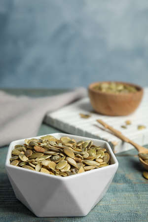 Bowl of raw pumpkin seeds on blue wooden table. Space for text Фото со стока