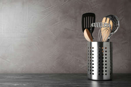 Holder with kitchen utensils on grey table against grey stone background. Space for text Imagens