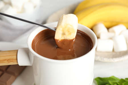 Dipping banana into fondue pot with chocolate on white wooden table, closeup