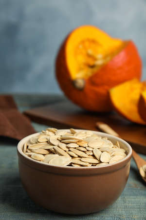 Bowl of raw pumpkin seeds on blue wooden table