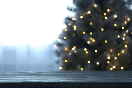 Blurred view of beautiful Christmas tree with yellow lights near window indoors, focus on wooden table. Space for text