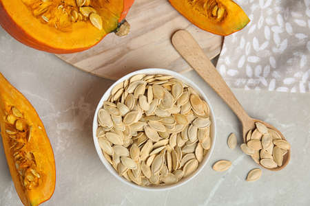 Flat lay composition with raw pumpkin seeds on light grey marble table