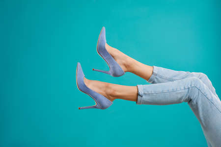 Woman in elegant shoes on light blue background