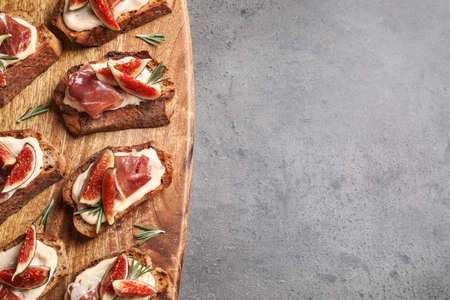Bruschettas with cream cheese, prosciutto and figs on grey table, above view. Space for text
