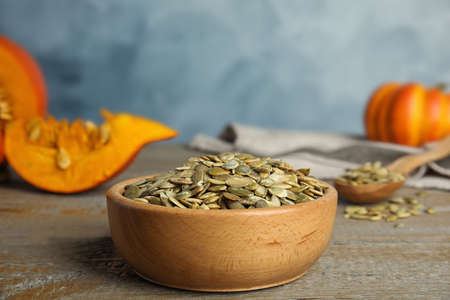 Bowl of raw peeled pumpkin seeds on wooden table against blue background. Space for text Фото со стока