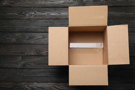 Open cardboard box on black wooden background, top view. Space for text