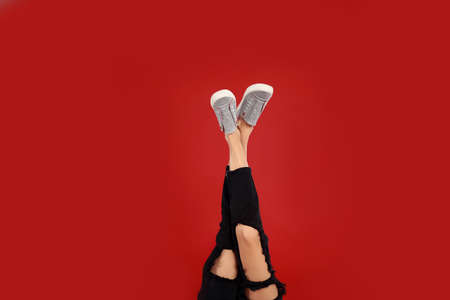 Woman in stylish sport shoes on red background
