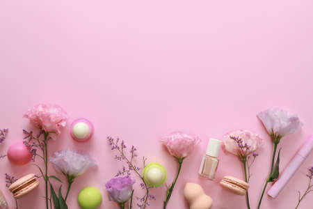 Flat lay composition with flowers and accessories on pink background, space for text. Beauty bloggers workplace