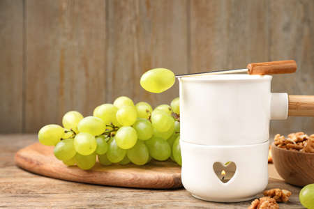 Fondue pot and grapes on wooden table