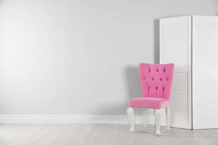 Stylish pink chair and folding screen near white wall. Space for text 写真素材
