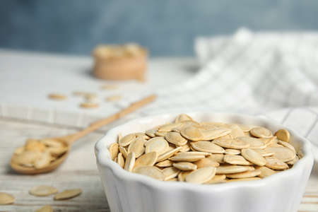 Bowl of raw pumpkin seeds on white wooden table, closeup. Space for text Фото со стока