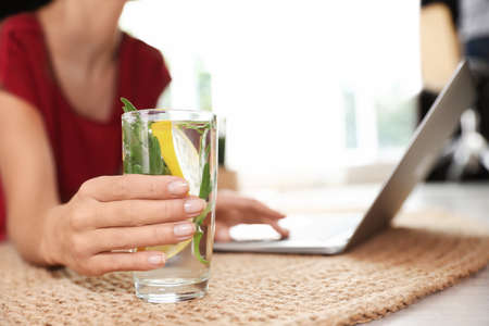 Young woman with glass of lemonade working on laptop at home, closeup. Refreshing drink Фото со стока