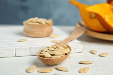 Spoon of raw pumpkin seeds on white wooden table
