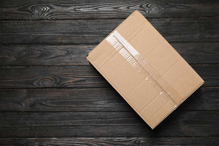 Closed cardboard box on black wooden background, top view. Space for text 写真素材