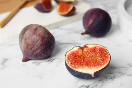 Tasty ripe fig fruits on marble table