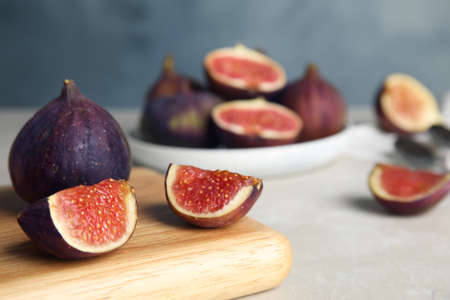 Wooden board with tasty figs on light grey marble table, closeup. Space for text Stockfoto - 130074956