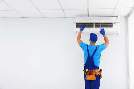 Professional technician maintaining modern air conditioner indoors. Space for text