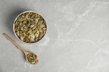 Raw pumpkin seeds on light grey marble table, flat lay. Space for text Фото со стока