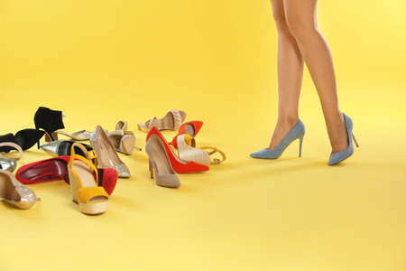 Woman trying on different high heel shoes on yellow background, closeup Stok Fotoğraf