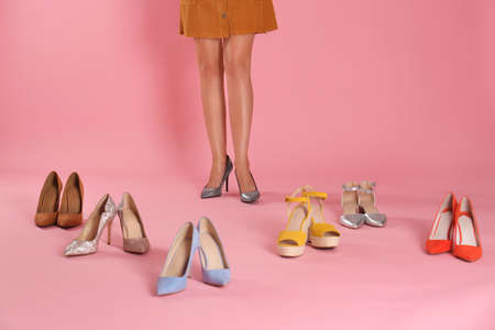 Woman trying on different high heel shoes on pink background, closeup Zdjęcie Seryjne