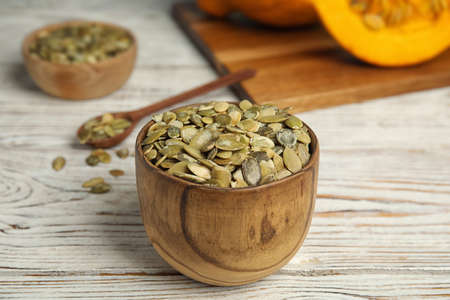 Bowl of raw pumpkin seeds on white wooden table Фото со стока