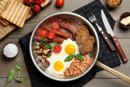 Traditional English breakfast with eggs served on wooden table, flat lay Stok Fotoğraf