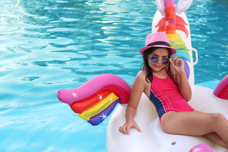 Happy cute girl on inflatable unicorn in swimming pool 免版税图像