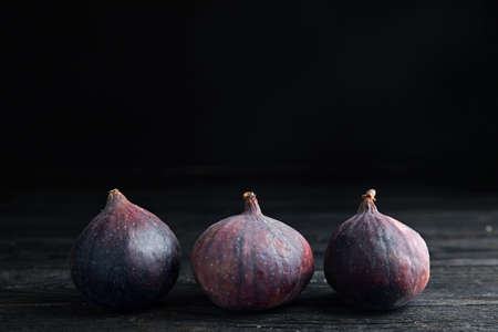 Tasty ripe figs on black wooden table against dark background. Space for text Stockfoto