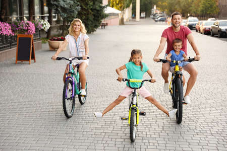 Happy family with children riding bicycles in city