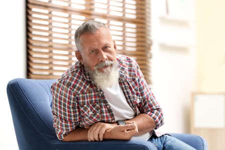 Portrait of handsome mature man sitting in armchair indoors Banco de Imagens