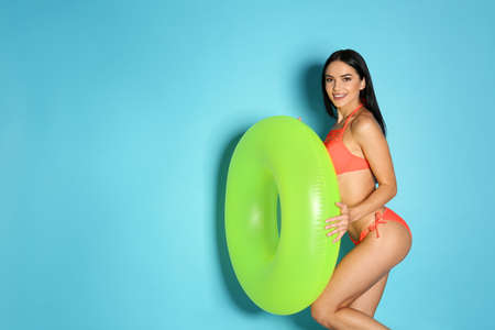 Beautiful young woman in stylish bikini with green inflatable ring on light blue background. Space for text 免版税图像