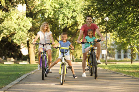 Happy family with children riding bicycles in park Banco de Imagens