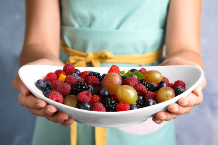 Woman holding plate of fresh tasty fruit salad against blue background, closeup Stock Photo